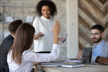 Close up ambitious female employee raise hand ask question to presenter at meeting. Woman show...