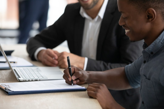 Close up happy african american businessman signing partnership agreement. Focused male on putting signature, concluding official contract with partner. Diverse man entrepreneur making profitable deal