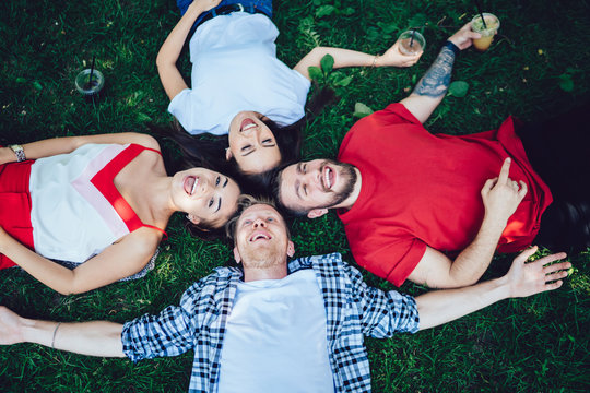 Laughing friends lying on lawn
