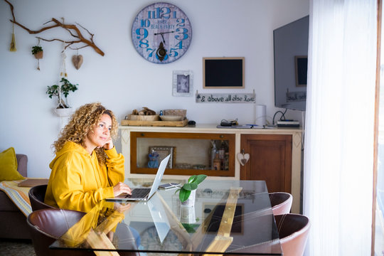 Beautiful young adult woman at home with personal laptop computer work and use modern internet technology - concept of smart work and alternative office for freelance people