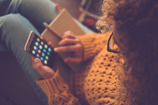 Closeup of woman viewed from above using a smart phone at home for work or social media sharing life activity - focus on eyeglasses and defocused background - yellow colors