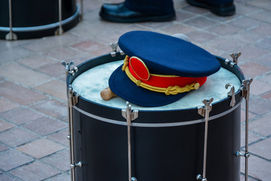 A military cap on top of a drum, street orchestra