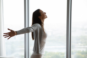 Happy young woman stand near window breathe fresh air stretch exercise in bedroom, smiling millennial girl overjoyed welcome new sunny morning at home or hotel, optimism, happiness concept Fotomurales