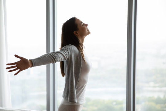 Happy young woman stand near window breathe fresh air stretch exercise in bedroom, smiling millennial girl overjoyed welcome new sunny morning at home or hotel, optimism, happiness concept
