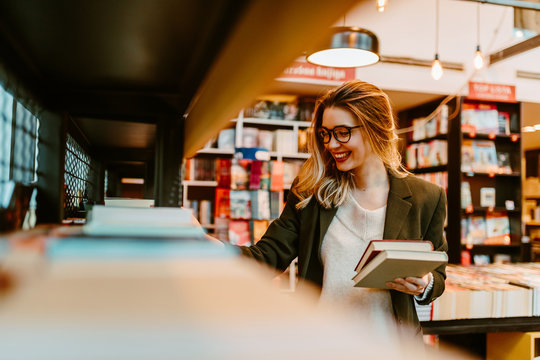 Portrait of young blonde woman with beautiful smile trying to find new books to read. Young woman is looking at book shelves in order to find something interesting for her to read.