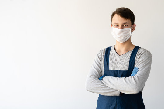 young man is wearing a medical face shield and uniform. Work during a pandemic and quarantine.