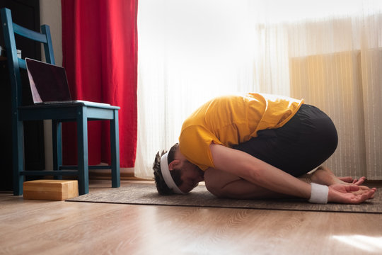 Young sporty man practicing online yoga lesson at home , doing Child exercise
