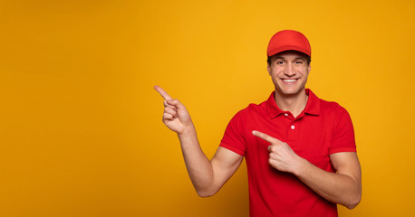 Handsome young happy courier or delivery man in red uniform is posing isolated on yellow background.