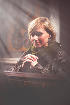 Retro styled image of beautiful blonde woman praying in churches. Religion, faith, meditation concept.