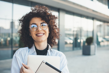 Close up portrait of a caucasian woman with curly hair and glasses holding a laptop and tablet while posing outside