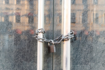 Lockdown shop market closed due to coronavirus pandemic door locked with chain. Bankruptcy of a...