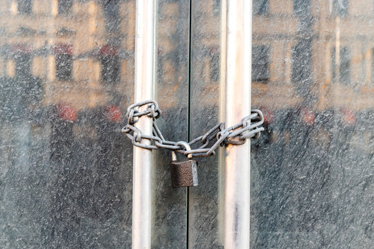 Lockdown shop market closed due to coronavirus pandemic door locked with chain. Bankruptcy of a business during long quarantine