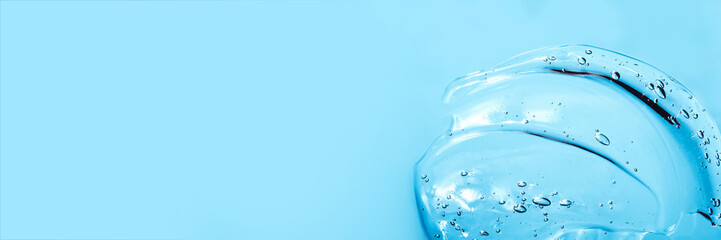 Hyaluronic acid cosmetic gel. Gel texture with bubbles on a blue background. Transparent smear of gel Banner Fototapete