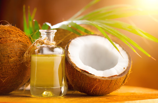 Coconut palm oil in a bottle with coconuts and green palm tree leaf on brown background. Coco nut closeup. Healthy Food, skin care concept. Vegan food. Skincare treatments. Aromatherapy.