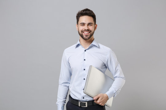 Smiling young unshaven business man in light shirt posing isolated on grey wall background studio portrait. Achievement career wealth business concept. Mock up copy space. Hold laptop pc computer.