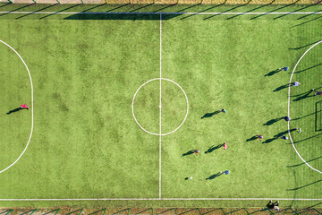 Top down aerial view of green football sports field and players playing football. Drone taken image of small unrecognizable sportsmen on grass covered stadium during sport activities.
