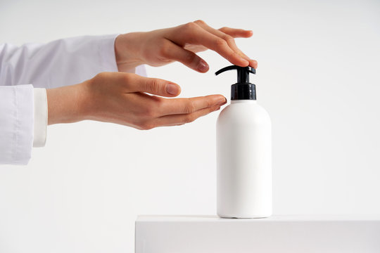 Woman hands pushing pump plastic soap bottle with copy space, using wash hand sanitizer gel pump dispenser. killing germs, bacteria and virus