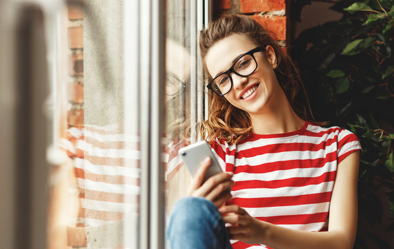 Young pleased woman using smartphone near window.