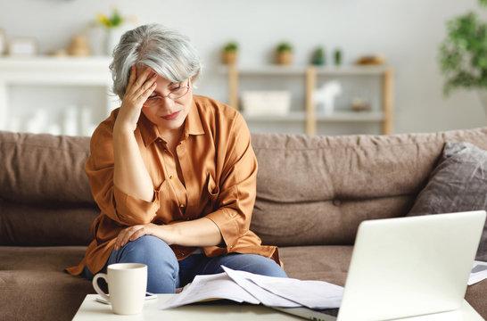 Stressed senior freelancer reading document.