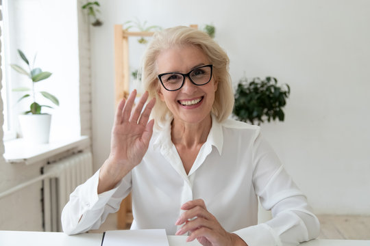 Close up headshot portrait picture of happy 60 years old businesswoman sitting by table. Smiling attractive young mature woman mentor greeting looking at camera in office.