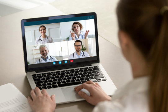 View over client shoulder sit at desk receive medical consultation on-line from diverse specialists. Woman listen doctors about corona virus precautionary measures, videoconference laptop webcam view