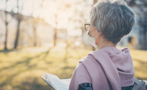 Senior lady with face mask reading the bible in front of a church