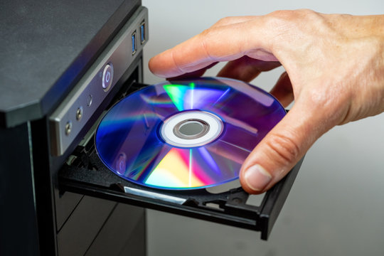 Hand inserting DVD into a computer. Closeup.