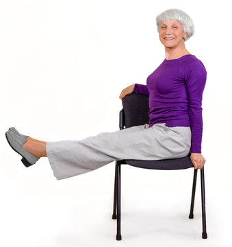 Happy charming beautiful elderly woman doing exercises at home on a chair. Workout gymnastics for health. On a white background
