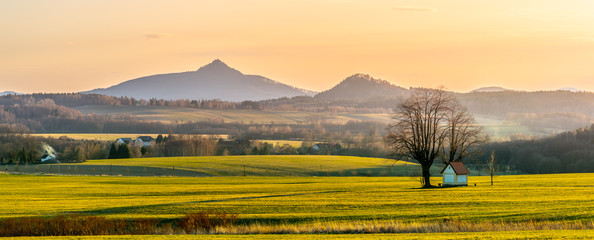 Hilly landscape with small chapel under the tree illuminated by evening sunset. Green grass fields and hills on the horizont. Vivid spring rural countryside. Ralsko Mountain, Czech Republic Fotomurales