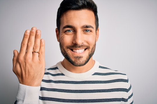 Handsome man with beard showing alliance ring marriage on finger over white background with a happy face standing and smiling with a confident smile showing teeth