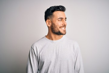 Young handsome man wearing casual t-shirt standing over isolated white background looking away to side with smile on face, natural expression. Laughing confident.