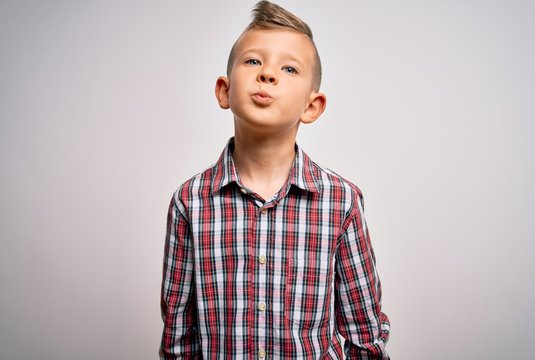 Young little caucasian kid with blue eyes wearing elegant shirt standing over isolated background looking at the camera blowing a kiss on air being lovely and sexy. Love expression.