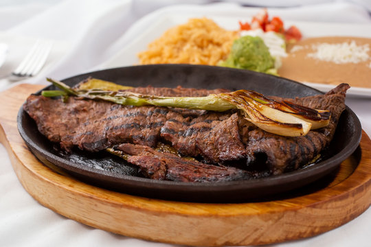 A view of a carne asada skillet plate, with a side of rice and beans, in a restaurant or kitchen setting.