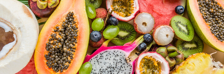 Fresh exotic fruits and tropical palm leaves on pastel orange background - papaya, mango, pineapple, passion fruit, dragon fruit, grapes, lichee, kiwi, melon. Healthy food and diet concept Wall mural