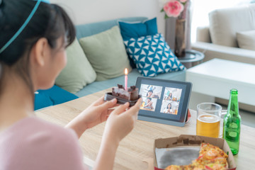 Asian woman virtual happy hour meeting birthday party with cake online together with her friend in video conference with digital tablet for a online meeting in video call for social distancing. Fotobehang