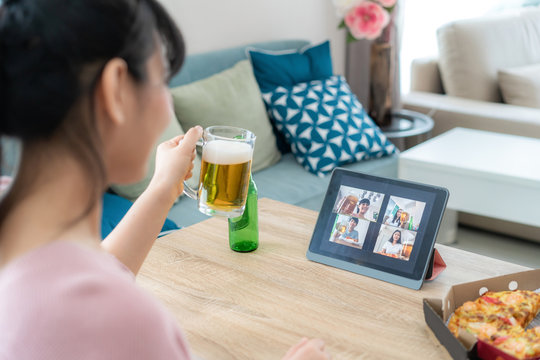Asian woman virtual happy hour meeting party and drinking alcohol beer online together with her friend in video conference with digital tablet for a online meeting in video call for social distancing.