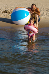 Watchful parent makes sure his little girl is safe at the beach as she wades into the water