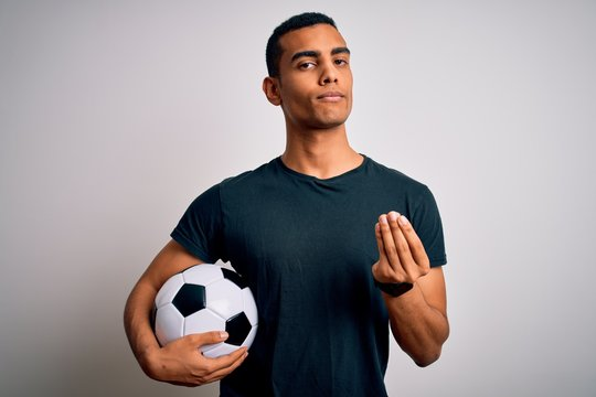 Handsome african american man playing footbal holding soccer ball over white background doing money gesture with hands, asking for salary payment, millionaire business