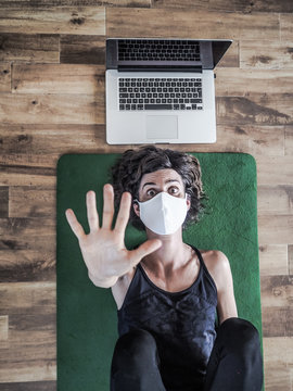 bird view of proud woman wearing a medical face to protect from corona covid-19 mask saying stop with hand lying on on a green yoga mat on wooden floor on her back with laptop after yoga workout