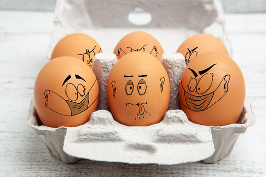 Not complying with social distancing rules and wearing face mask in public - concept depicted with faces illustrated on eggs