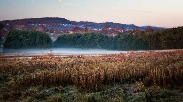 A foggy meadow with fall foliage decorating a series of hills in Berks County, PA