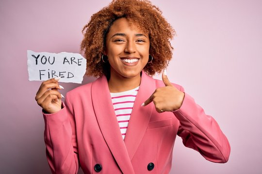 Young African American afro woman with curly hair holding papaer with you are fired message with surprise face pointing finger to himself