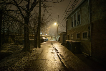 Wall Mural - Dark and eerie urban city alley at night with snow in the winter