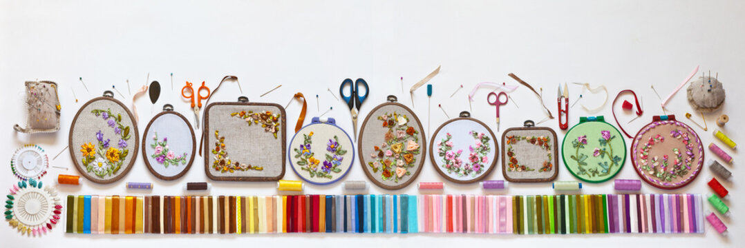 Needlework and embroidery. Panoramic top view of different types of embroideries with satin ribbons. All embroideries are made by author of photo. All of them are already individually in my portfolio