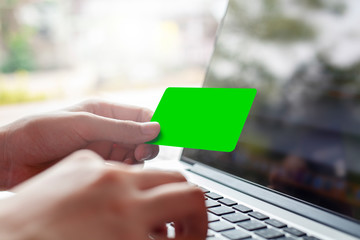 hand holding blank green credit card and using modern laptop, typing and texting. against defocus green nature outdoor.  mobile payment ,online shopping concept