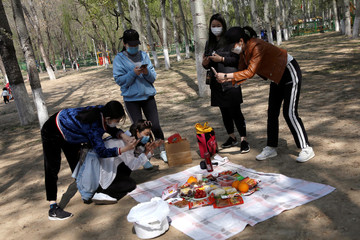Women wearing face masks take pictures of their picnic food after they arranged them on a sheet at a park during Chinese Qingming festival holiday in Beijing