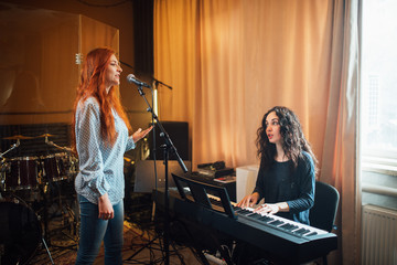 student girl sings in a vocal lesson to accompaniment of a teacher on an electronic keyboard