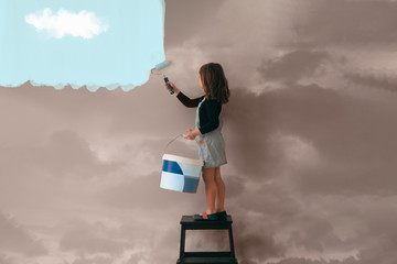 little girl uses a can of paint to color the wall of the room from cloudy gray to clear blue sky - positive attitude, vibes and mentality concept