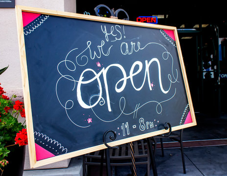 Chalk sign at resturant in welcoming artisitic cursive writing stating Yes We Are Open