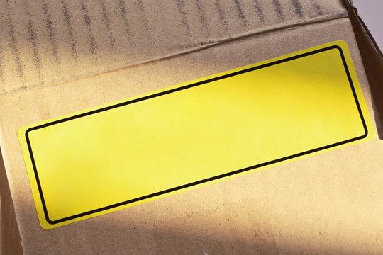blank yellow label sticker tab of warning sign on carton paper box